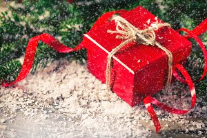 Red Christmas present box with fir and snow wood