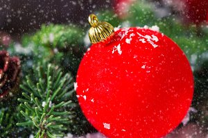 Red Christmas bauble with snow on wood