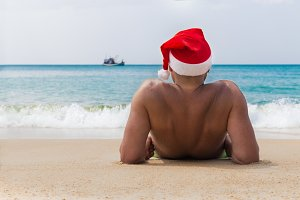 Man in Christmas red hat on tropic beach