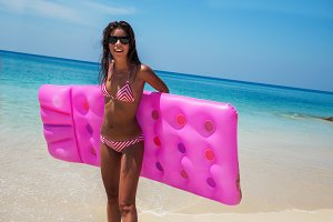 slim brunette woman sunbathe with an air mattress