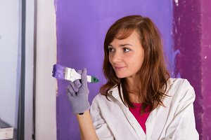 Woman paints wall by purple roller
