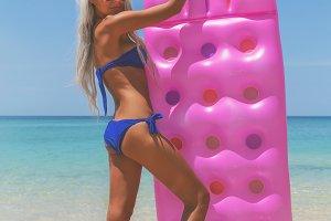 Slim blonde woman with air mattress tropic beach