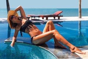 slim woman in s straw hat and sunglasses sunbath