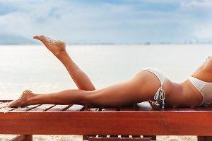 beautiful young slim woman legs sunbathe on beach