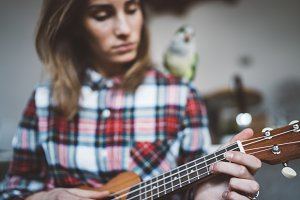 Hipster girl playing ukulele guitar