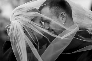 Bride and groom hidden under a veil