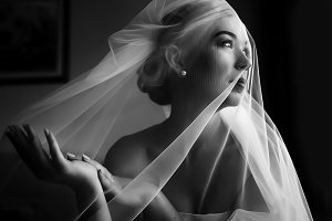 Tender veil coveres bride's face