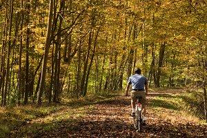 Senior cyclist on forest trail