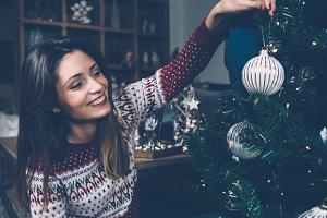 Smiling girl hanging bauble on Christmas tree