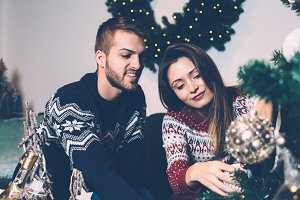 Smiling couple decorating fir tree