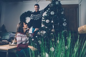 Couple at home decorating Christmas tree