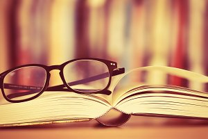 Close up eyeglasses and opened book