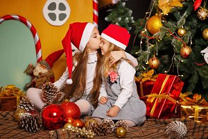 Sister kissing her sister. Christmas