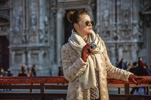 woman in Milan looking into distance while holding photo camera