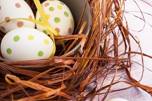 Composition with Easter eggs in nest, on wooden background