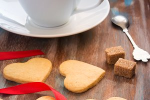 Wooden tray with a cup of coffee and biscuits in the shape of he