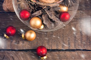 Pine cones, nuts and Christmas toys in the glass on a wooden background.