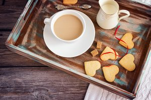Valentine cookies and a cup of coffee with cream on a wooden pla