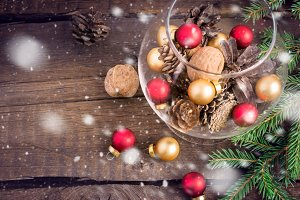 Christmas toys, nuts, fir cones and twigs on a wooden background