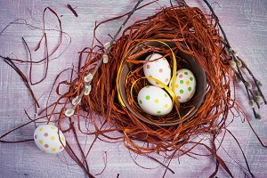 Easter composition with colored eggs in a nest