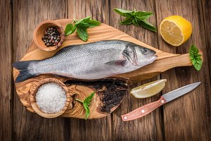Seabass fish on the wooden board.