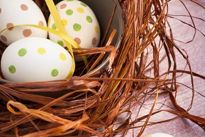 Composition with Easter eggs in nest, on  pink  batskground, tin