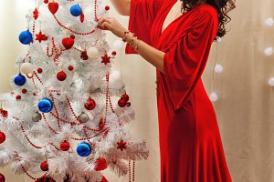 Girl in red dress. Christmas tree
