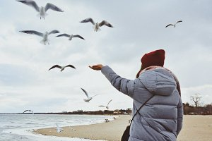 Girl at the sea with seagulls around