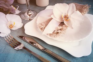 Vintage table setting with orchid decorations on a blue background. Tinted.