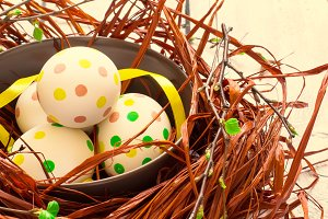 Composition with Easter eggs in nest, on white background with b