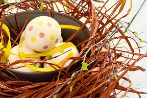 Composition with Easter eggs in nest, on boards background