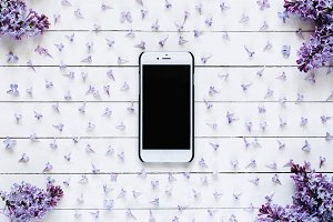 Smartphone and lilac flowers