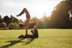 Strong young couple doing acroyoga