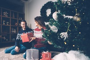 Young couple with presents on carpet