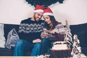Young couple in Santa hats using phone