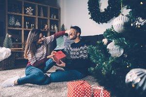 Woman closing eyes to boyfriend giving present