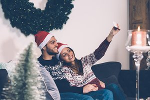 Young couple in Santa hats making selfie