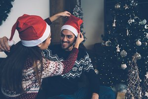 Loving couple trying Santa hats on
