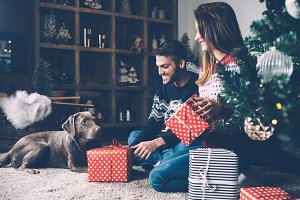 Laughing couple with presents and dog