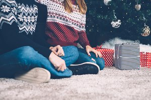 Crop couple sitting on carpet with presents