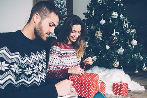 Couple unwrapping present