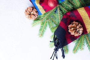 Fir tree branches in woolen scarf pine cones and baubles