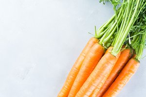 Fresh carrots on gray background. Vertical. Copy space