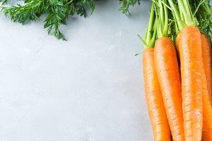 Fresh organic carrots on gray background