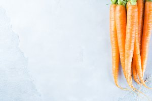 Gray background with fresh raw carrots