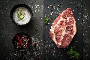Raw pork steak on black