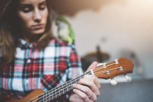 Hipster girl learning to play guitar