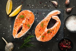 Raw salmon steak with food ingredients.