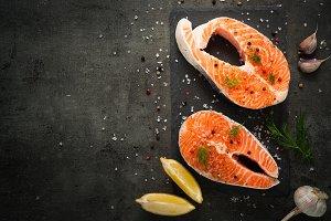 Raw salmon steak with food ingredients.