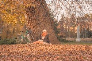 Woman sitting leaves autumn park